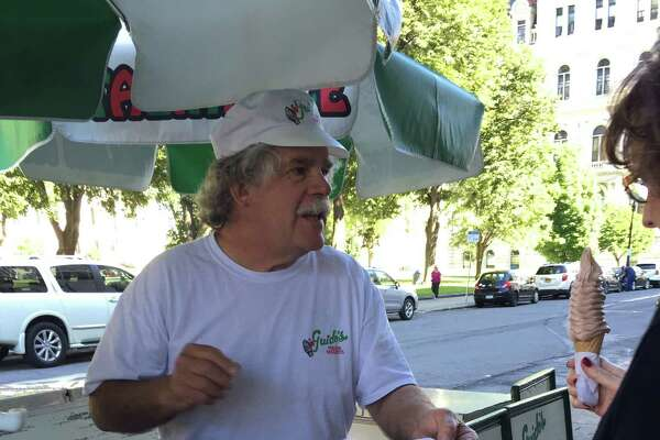 Mark Guido, who has had his frozen yogurt and Italian ice cart in front of the Legislative Office Building since 1981 and five governors, serves up a chocolate frozen yogurt cone Wednesday in between conversations with state employees about Wedneday's federal indicments on political corruption in Albany (Paul Grondahl / Times Union)