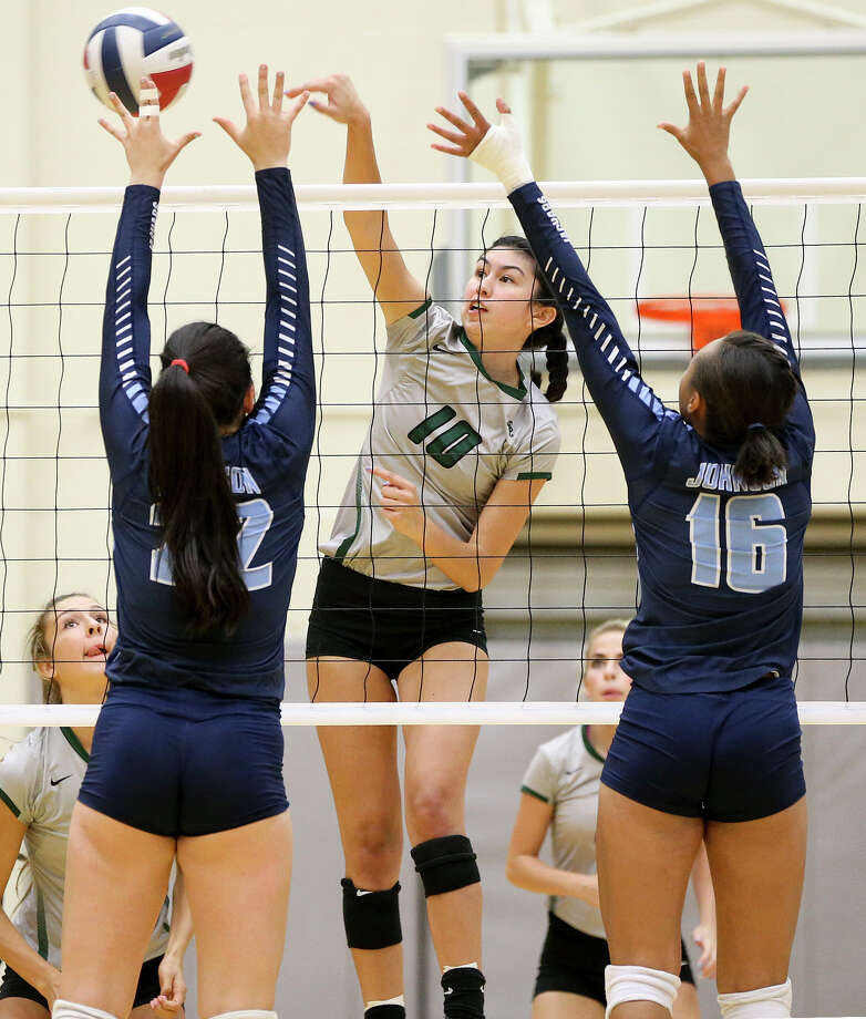 Reagan's Izzy DeLaRosa hits the ball past Johnson's Julia Deais (left) and Chloe Lucas-Brown during their District 26-6A match at Littleton Gym on Friday. Reagan seized control of first place in District 26-6A with the crucial victory. Photo: Marvin Pfeiffer / San Antonio Express-News / Express-News 2016