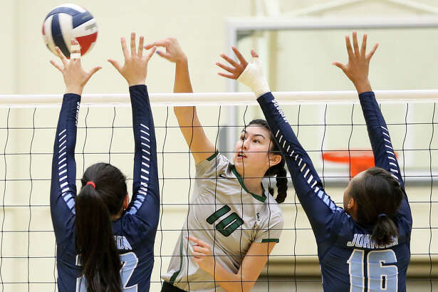 Reagan's Izzy DeLaRosa hits the ball past Johnson's Julia Deais (left) and Chloe Lucas-Brown during their District 26-6A match at Littleton Gym on Friday. Reagan seized control of first place in District 26-6A with the crucial victory.
