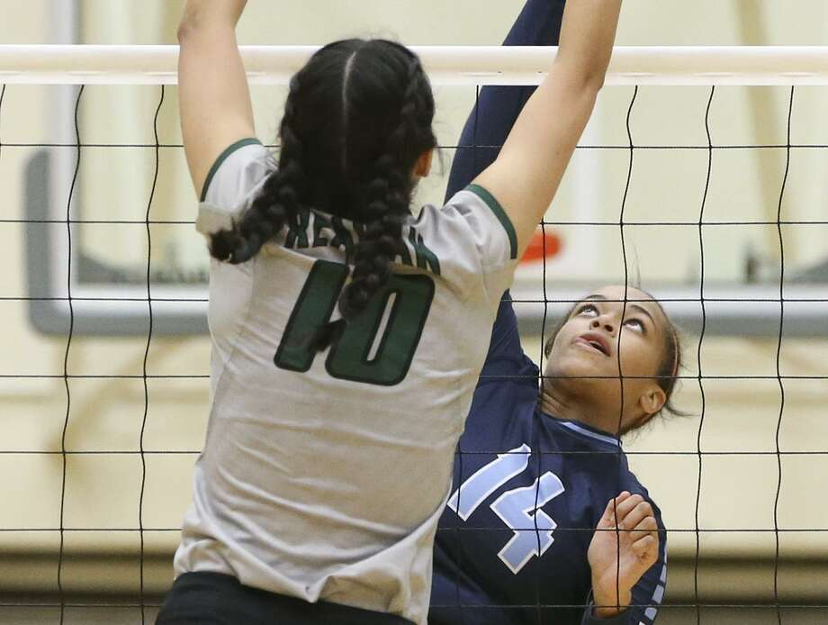 Reagan's Izzy DeLaRosa (left) goes up to block a shot by Johnson's Kaylyn Winkler during a District 26-6A match at Littleton Gym on Sept. 23, 2016. Photo: Marvin Pfeiffer /San Antonio Express-News / Express-News 2016