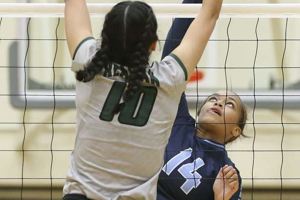 Reagan's Izzy DeLaRosa (left) goes up to block a shot by Johnson's Kaylyn Winkler during a District 26-6A match at Littleton Gym on Sept. 23, 2016.