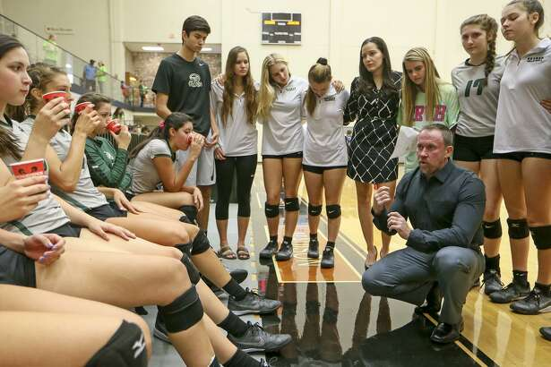 Reagan coach Mike Carter talks to the Lady Rattlers during a timeout in their District 26-6A match with Johnson at Littleton Gym on Sept. 23, 2016.