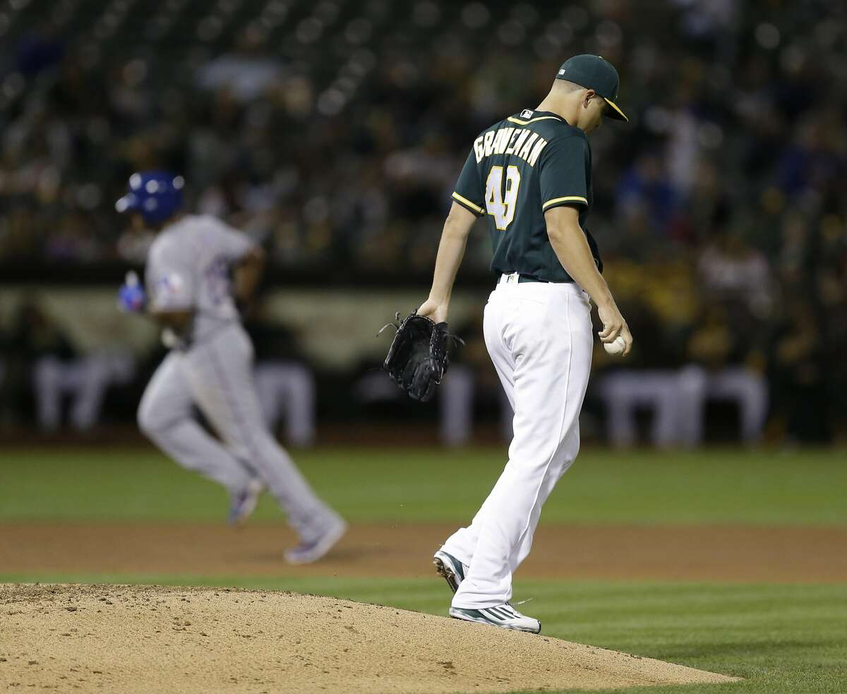 Oakland Athletics pitcher Kendall Graveman, right, walks off the mound after giving up a two run home run to Texas Rangers' Adrian Beltre, left, in the seventh inning of a baseball game Friday, Sept. 23, 2016, in Oakland, Calif. (AP Photo/Ben Margot)