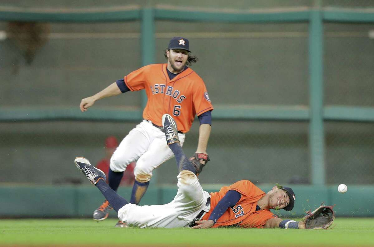 Houston Astros shortstop Carlos Correa (1) falls as he can't get to a hit by Los Angeles Angels left fielder Rafael Ortega (39) in the ninth inning. Photos of MLB game action between Houston Astros and Los Angles Angels on Friday, Sept. 23, 2016, at Minuet Maid Park in Houston.