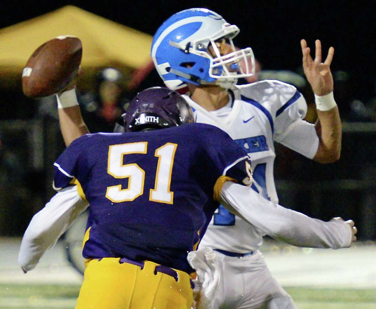 Shaker QB #14 Wahid Nabi gets pressured by Troy defender #51 Derrick Cipriani during Friday's game at Troy High Friday Sept. 23, 2016 in Troy, NY. (John Carl D'Annibale / Times Union)