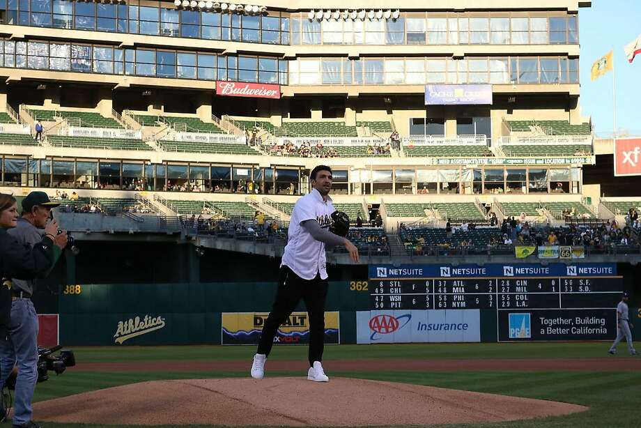 Warriors center Zaza Pachulia throws out the first pitch at Friday's A's-Rangers game. Photo: Elizabeth Staub/Oakland Athletics