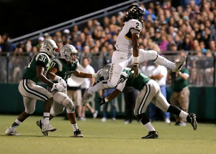 Panthers' Najee Harris, 2 hurdles the Spartan's Kairee Robinson, 25 on a first quarter run, as the Antioch Panthers high school football team takes on the Spartans of De La Salle in Concord, California on Fri. Sept. 23, 2016.