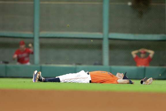 Houston Astros shortstop Carlos Correa (1) winces as he lays on the ground after a hard fall while trying to catch a hit by Los Angeles Angels left fielder Rafael Ortega (39) in the ninth inning.
