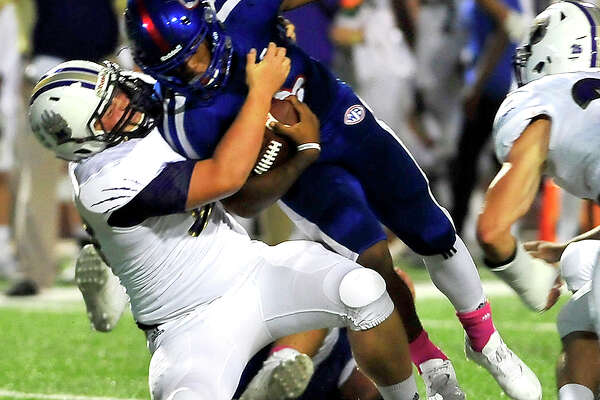 West Brook's Joel Denley is brought down by Montgomery's Wes May during Friday night's match-up at the Thomas Center. Photo taken Friday, September 23, 2016 Kim Brent/The Enterprise