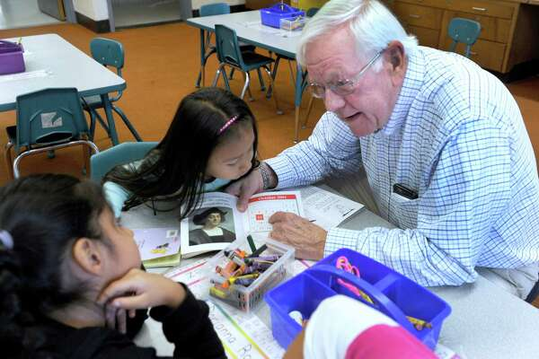 Charles Schott, of Brookfield, a volunteer mentor, works with Darianna Rodriguez, left, and Sheyla Valasquez, both 5, in a kindergarten class at Danbury's Morris Street School in this file photo from 2015.