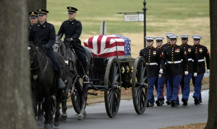 The casket of Marine Chief Warrant Officer 3 Gary L. Stouffer, of Hubert, N. C., is brought on a caisson to the burial site at Arlington National Cemetery in Arlington, Va., Dec. 7. Stouffer, 37, was among four veterans killed when the float they were on was hit by a train during a parade in Midland on Nov. 15. Photo: Susan Walsh