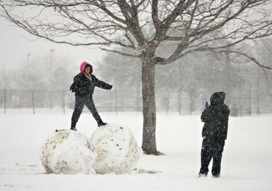 Victoria Luna poses for George Olivas on top of two giant snowballs at Album Eastwood Park as snow blankets the area Thursday in El Paso. Up to eight inches of snow, with isolated amounts approaching 10 inches, were expected across West Texas as the storm moved across the region. Photo: Fernie Castillo