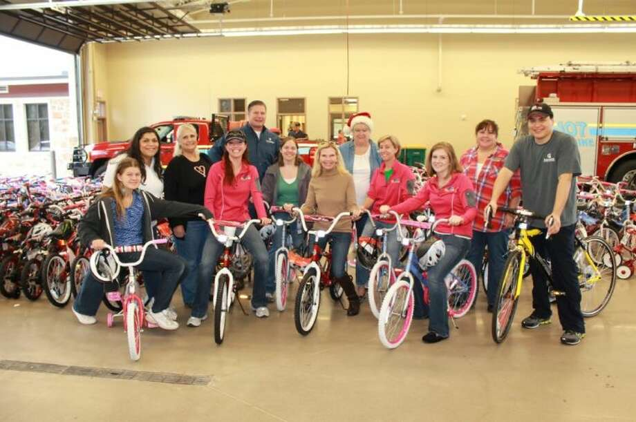 Keith Gordon (left, back row) joins Dr. Ann Snyder (center) and Interfaith staff and volunteers during the 2012 Bike Build donation benefiting Interfaith of The Woodlands Holiday Toy Distribution program.