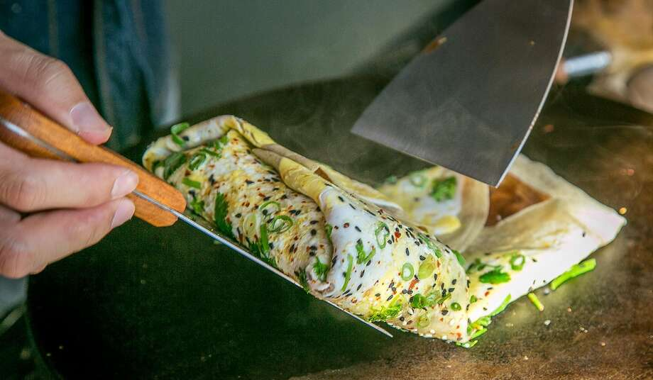 Cheng Hu rolls up a jianbing (Chinese crepes) at Tai Chi Jianbing in S.F. Photo: John Storey, Special To The Chronicle
