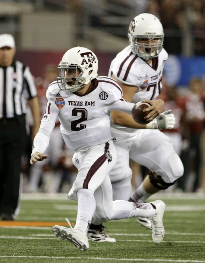 Texas A&M's Johnny Manziel finds running room against Oklahoma in the second half of the Cotton Bowl. The Aggies won 41-13. Photo: Tony Gutierrez