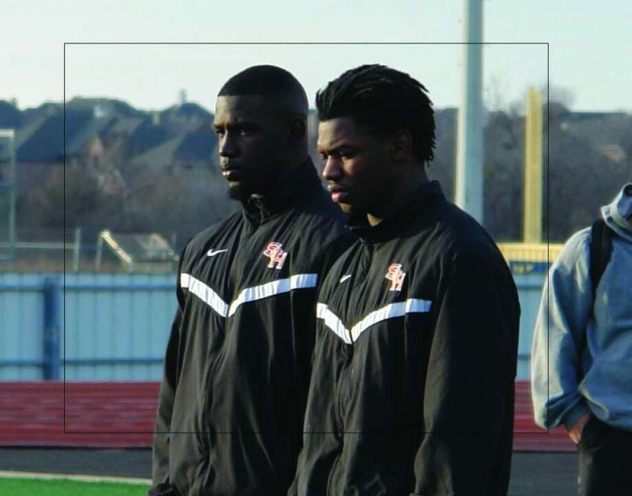 Conroe High School graduate Bookie Sneed, left, alongside a teammate, listens to a Sam Houston State defensive coach during Friday's practice at Wakeland High School in Frisco.