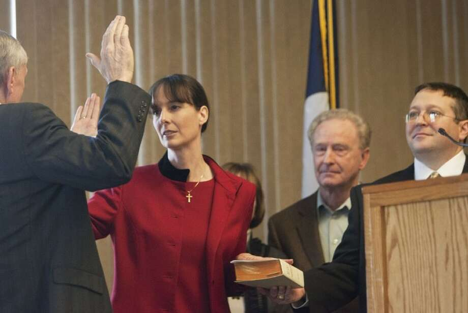 Claudia Laird is sworn in as County Court-at-Law 2 Judge by Jerry Winfree, who retired after serving in the position for 29 years, during Saturday's swearing-in ceremony at the Lone Star Convention Center in Conroe.