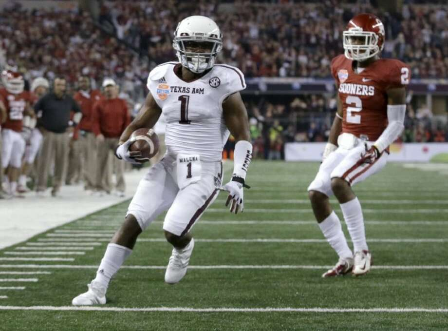 Texas A&M's Ben Malena steps into the end zone for a touchdown as Oklahoma's Julian Wilson watches in the second half of the Cotton Bowl. The Aggies won 41-13. Photo: LM Otero