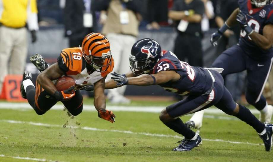 Texans cornerback Alan Ball, right, brings down Bengals kick returner Brandon Tate. The Texans eliminated the Bengals 19-13 in the AFC playoffs on Saturday. Photo: Jose Yau