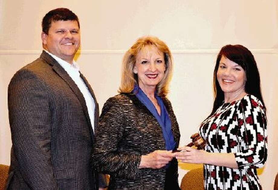 Greater Conroe/Lake Conroe Area Chamber of Commerce President Scott Harper looks on as outgoing Chairman Helen Thornton, center, passes the gavel of leadership to incoming Chairman Tamara Trow.