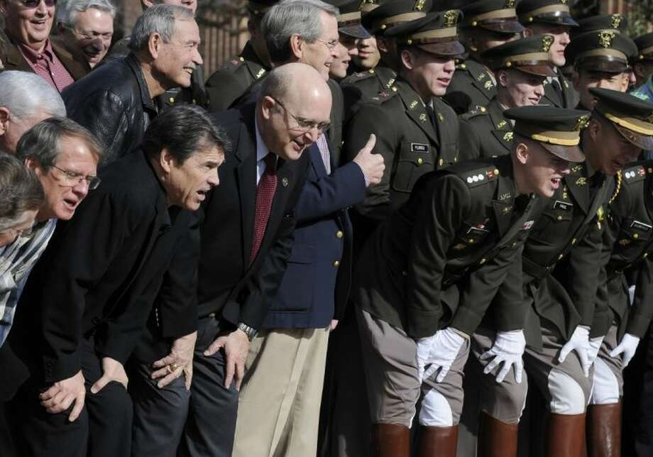Texas Gov. Rick Perry, second from lower left, joins former and present members of the Texas A&M Corps of Cadets Squadron 6 following ceremonies marking the reactivation of the unit Friday in College Station. Photo: Pat Sullivan / AP