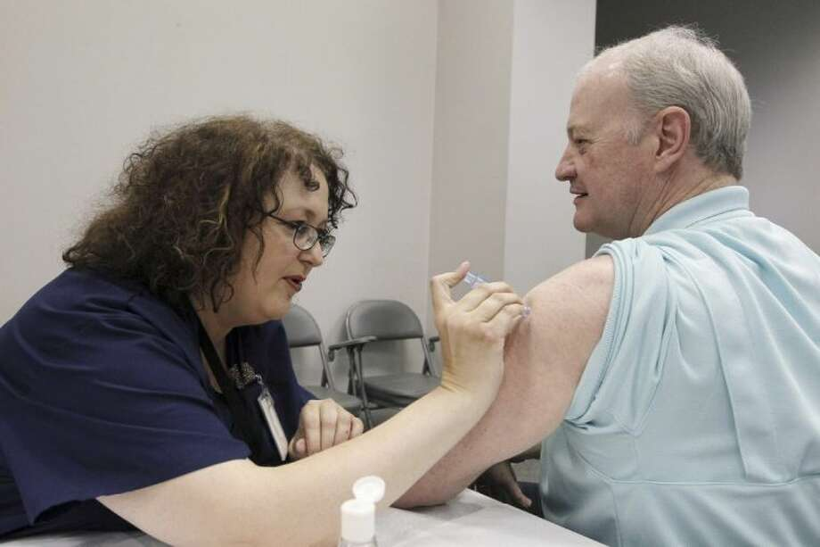 In this file photo taken Oct. 17, 2012, Bill Staples, a Mississippi Department of Health employee, is given a flu vaccine shot by registered nurse Rosemary Jones, also with the health department, in Jackson, Miss. Photo: Rogelio V. Solis / AP2012