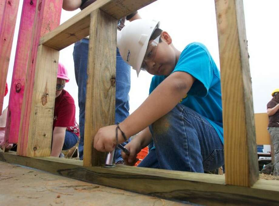Angel Adame, son of future homeowner Lourdes Adame, helps secure a wall frame into place during Saturday's build event in the Cedar Creek subdivision of Conroe.