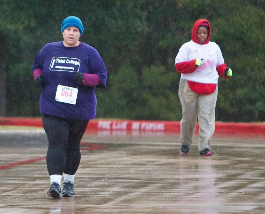 Kendra Willeby, left, braves the cold and rain as she nears the finish line during Saturday's Diva Dash fun run at Barbara Bush Elementary in The Woodlands. Photo: Staff Photo By Eric Swist