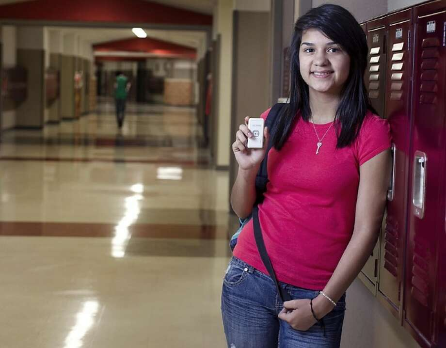 In this Dec. 11, 2012 photo, Marisol Castro Soto, 16, a sophomore at Akins High School, holds a student GPS tracker she uses to record her location and attendance at school in Austin, Texas. Photo: Rodolfo Gonzalez