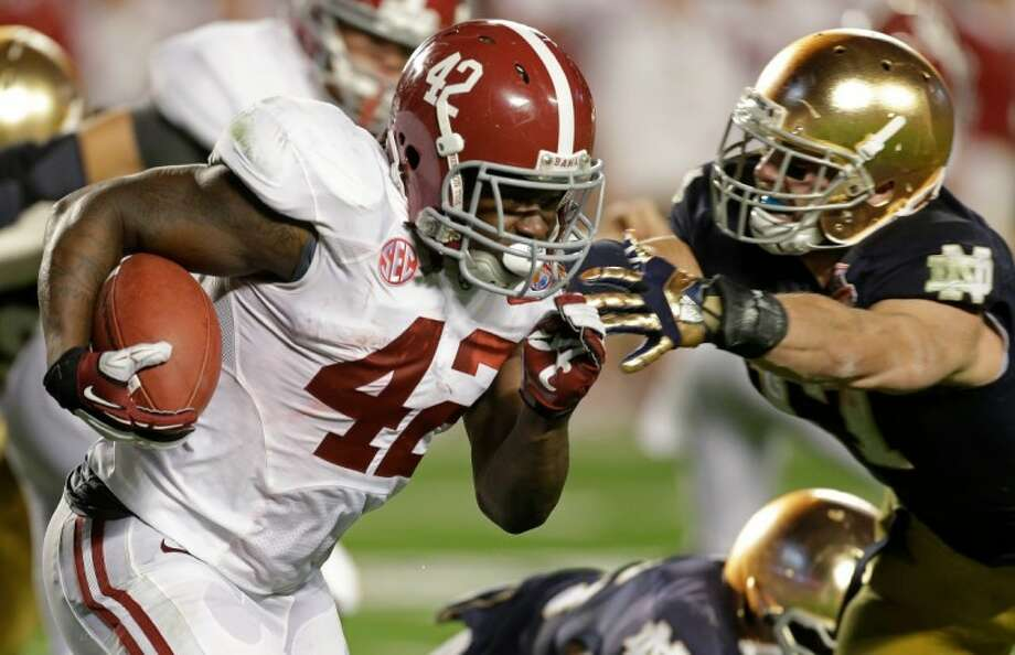 Alabama's Eddie Lacy runs for first-half yardage in the Crimson Tide's victory over Notre Dame in the BCS championship game. Photo: Chris O'Meara