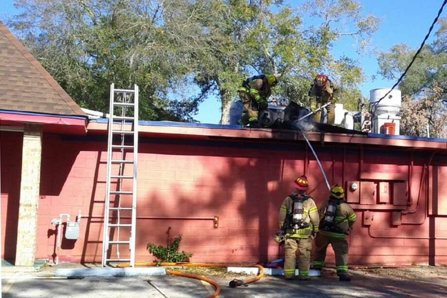 Conroe firefighters work to remove a smoking vent from the roof of the Baytown Seafood Restaurant, located at 1400 N. Frazier St., after a grease trap overheated before the restaurant opened Monday morning, causing smoke damage.