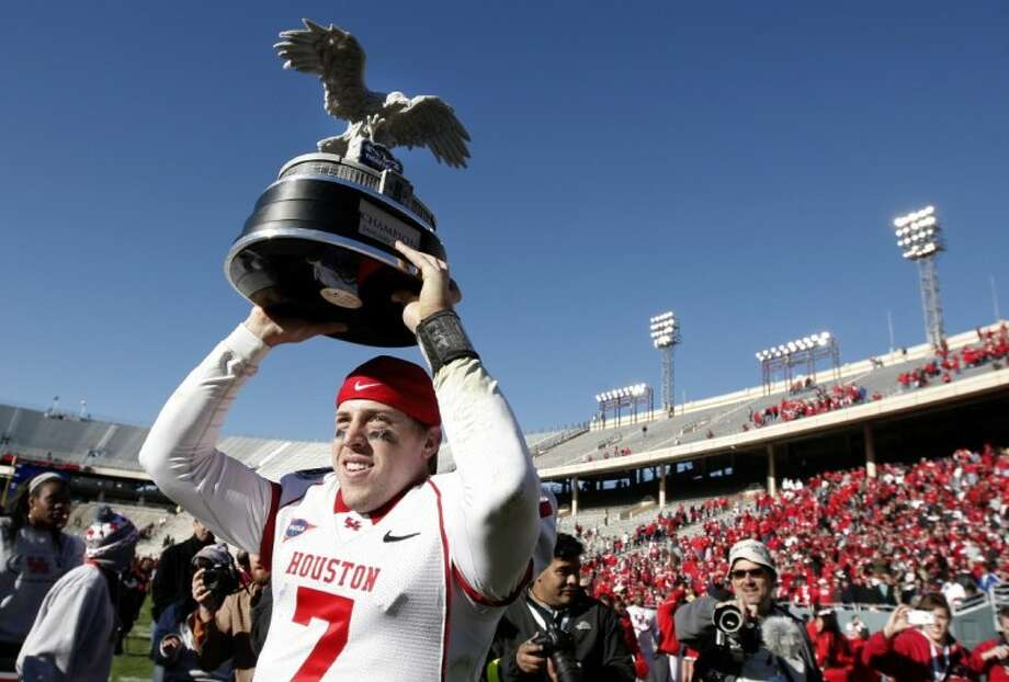 Houston quarterback Case Keenum celebrates with the championship trophy after defeating Penn State in the TicketCity Bowl Monday at the Cotton Bowl in Dallas. Photo: Brandon Wade