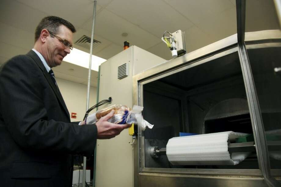 In this Dec. 6, 2012, photo, Don Stull, chief executive officer of Microzap, Inc., places a loaf of bread inside a patented microwave that kills mold spores in Lubbock, Texas. The company claims the technology allows bread to stay mold-free for 60 days. Photo: John Mone