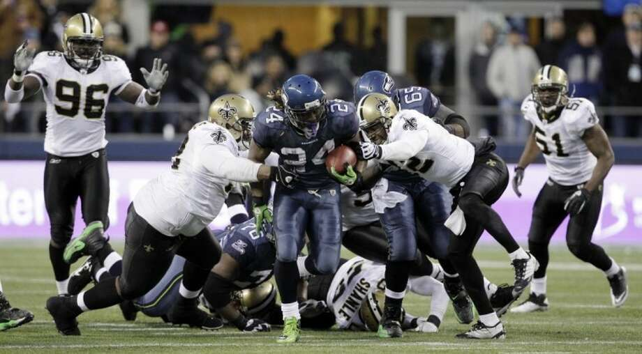 The Seattle Seahawks' Marshawn Lynch breaks away from a tackle by New Orleans Saints defenders to score the clinching touchdown in the second half of a Saturday's NFC wild card playoff game in Seattle.