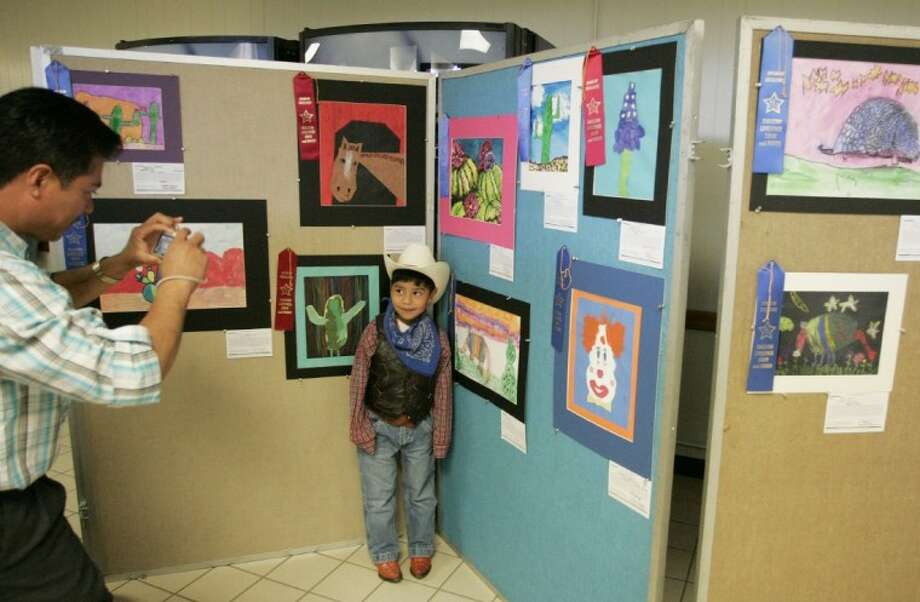 Creighton Elementary School kindergarten student Carlos Parra stands next to his painting as his father snaps a photo at the Conroe Independent School District Western Art Show Saturday at the Conroe High School Career and Technology Building.