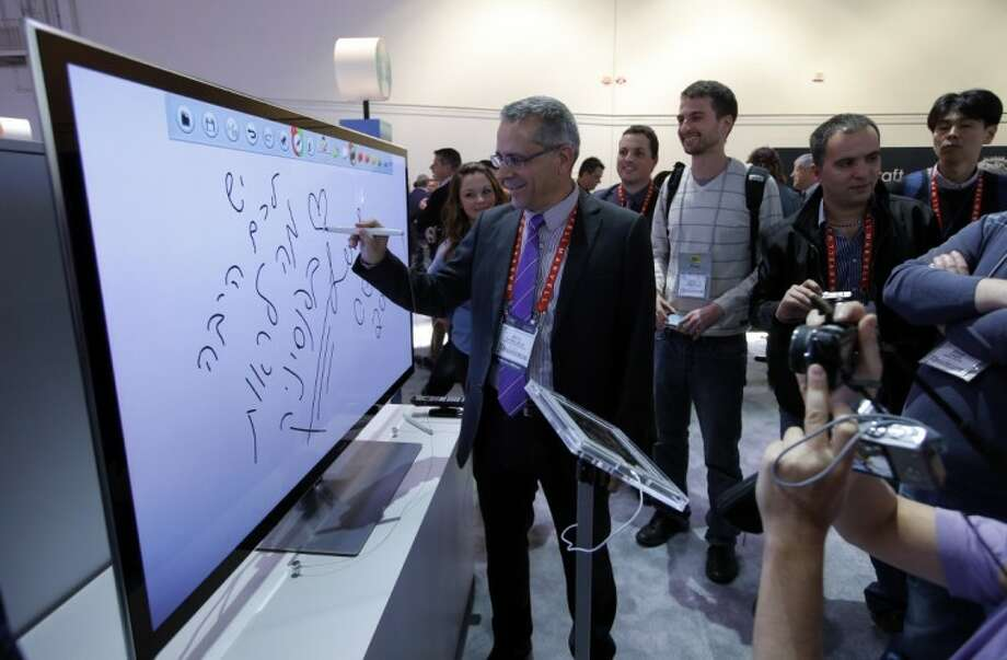 Moti Elmaliach, center, of Israel, writes on a display using Panasonic's electronic touch pen at the Panasonic booth at the International Consumer Electronics Show in Las Vegas, Tuesday, Jan. 8, 2013. Photo: Jae C. Hong