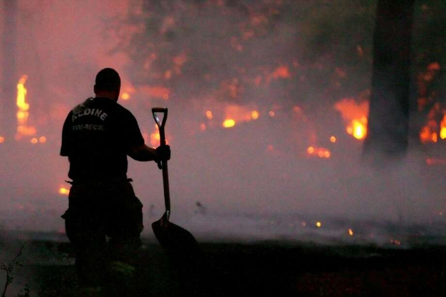 A firefighter battles a small part of the Tri-County Fire on FM 1774 near FM 1486 in Magnolia. Nearly 8,000 residents were evacuated from the area in early fall due to the fire that destroyed nearly 20,000 acres. Photo: Karl Anderson