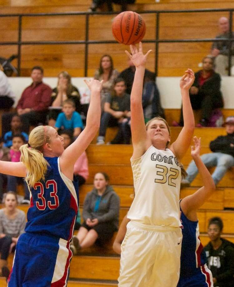 Conroe's Courtney Boatright goes up for a basket over Oak Ridge's Courtney Cassidy during Tuesday night's District 14-5A game in Conroe. Photo: Staff Photo By Eric Swist