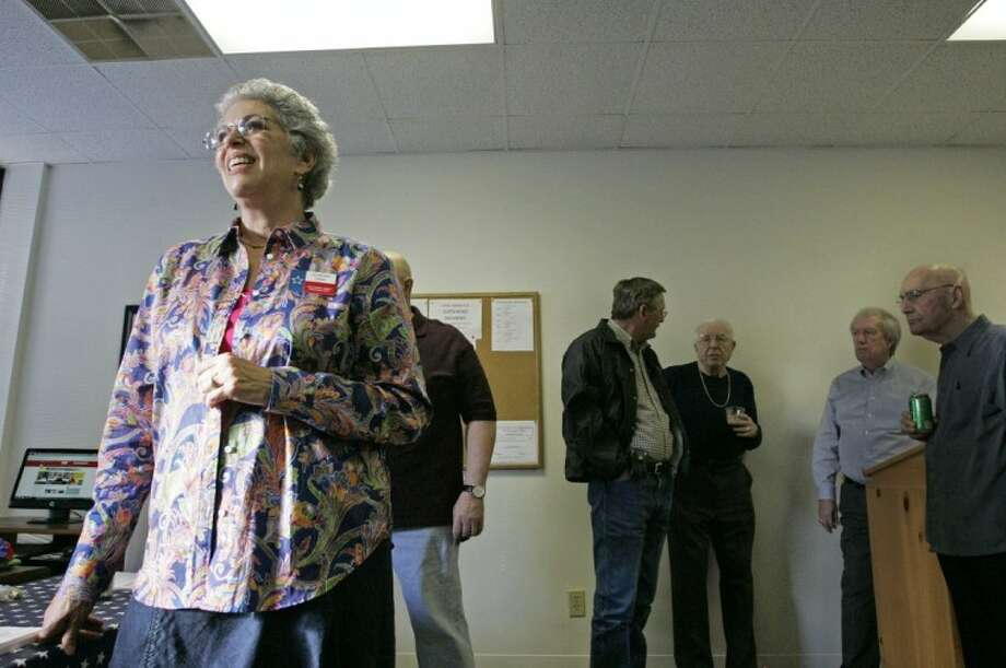 Montgomery County Democratic Party Chairwoman Adrienne Cadik speaks about the party's new headquarters as members mingle in the background Saturday in Conroe.