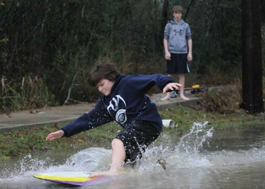 Connor Davis surfs with a skimboard as Wesley Howland looks on off Mill Branch Heavy Drive in Porter Wednesday. The boys were making the most of the heavy rains that hit much of Southeast Texas over the past two days, including dropping at least a couple of inches in Montgomery County. Photo: Jason Fochtman