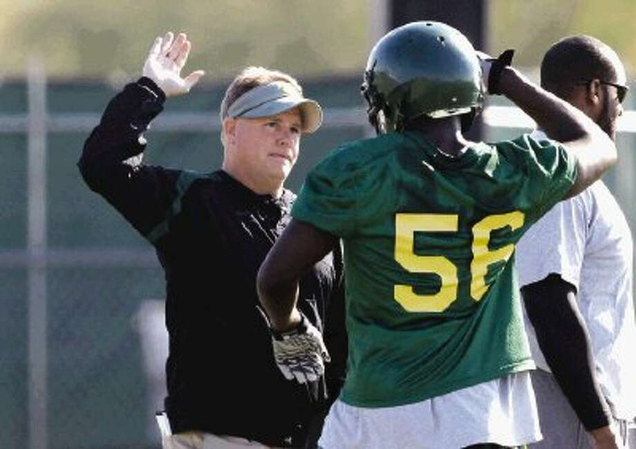 Oregon head coach Chip Kelly, left, high fives linebacker Josh Kaddu during practice before playing on Saturday in Scottsdale, Ariz. The BCS Championship game will be played on tonight at 7:30. / AP2011