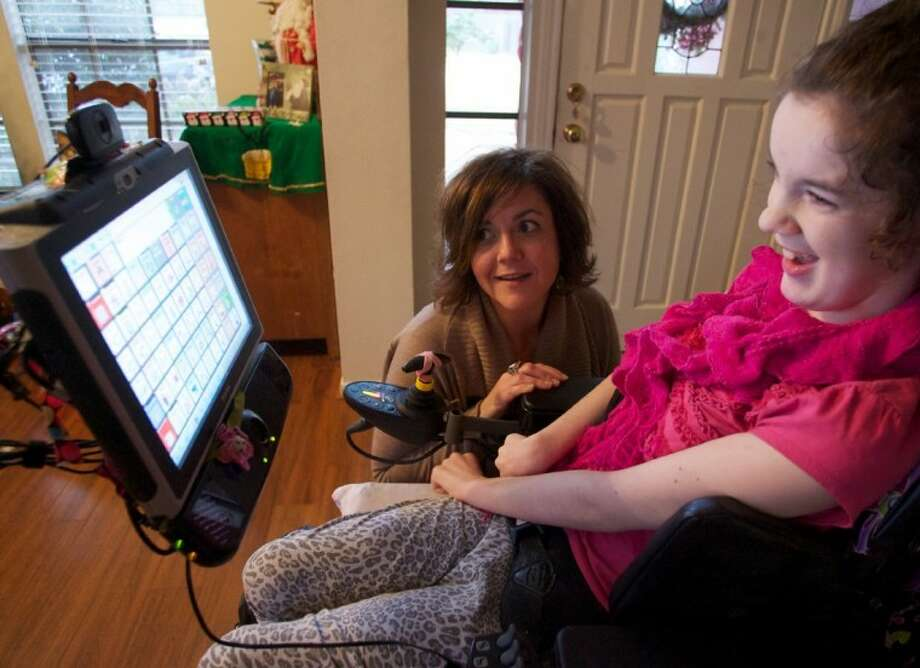 Megan Fry, who suffers from cerebral palsy, smiles alongside her mother Andrea at her home in The Woodlands as the pair demonstrate a custom computer and software that allow Megan to speak through the machine, controlling the computer with movements from her eyes. Photo: Staff Photo By Eric Swist