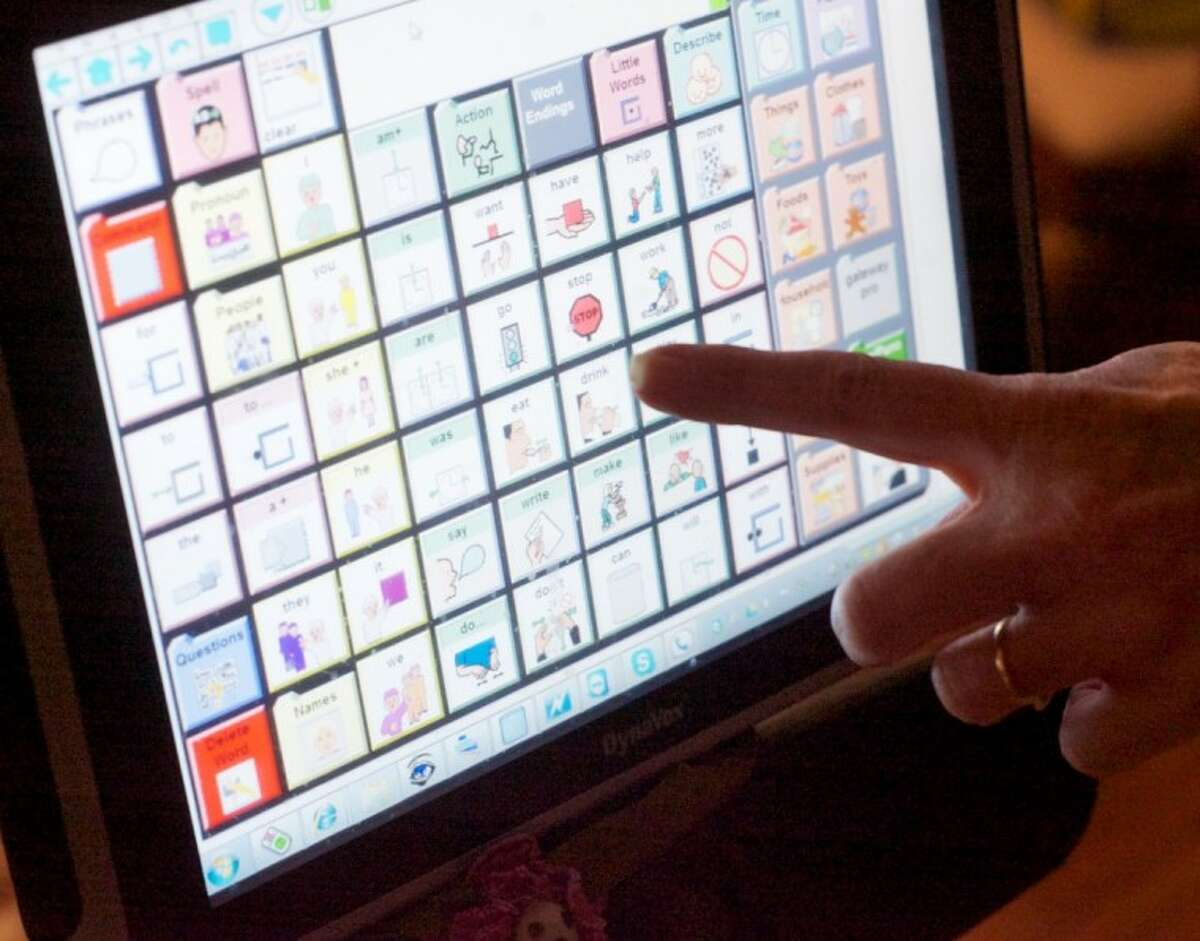 Andrea Fry points to custom icons on the computer of her daughter Megan, who suffers from cerebral palsy. The custom icons represent words and allow Megan to speak through the computer. She can control the computer using movements from her eyes.
