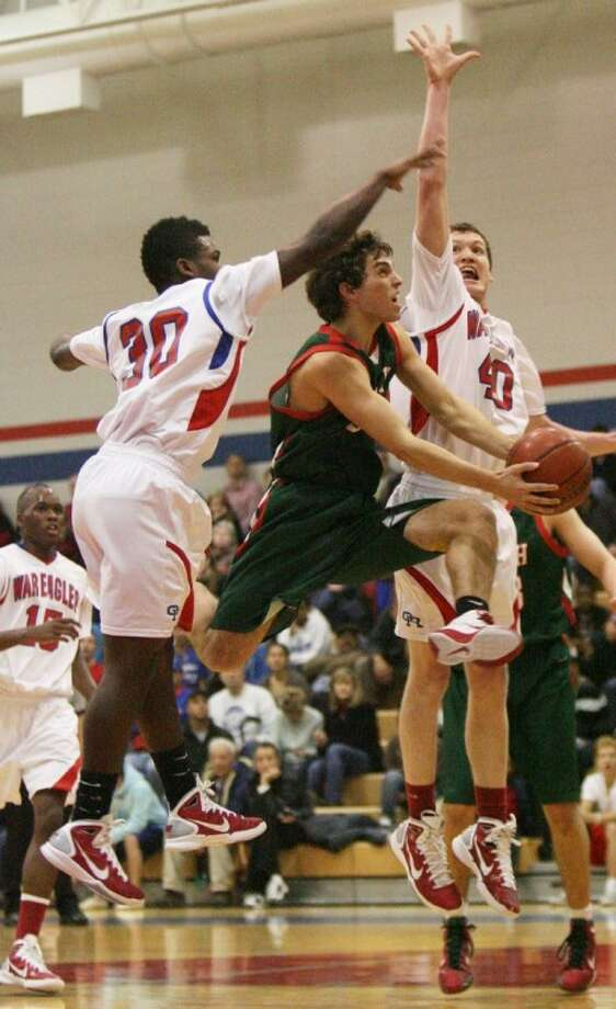 The Woodlands' Jordan Alpha drives to the basket as Oak Ridge defenders attempt to block during Tuesday night's district game at Oak Ridge High School.