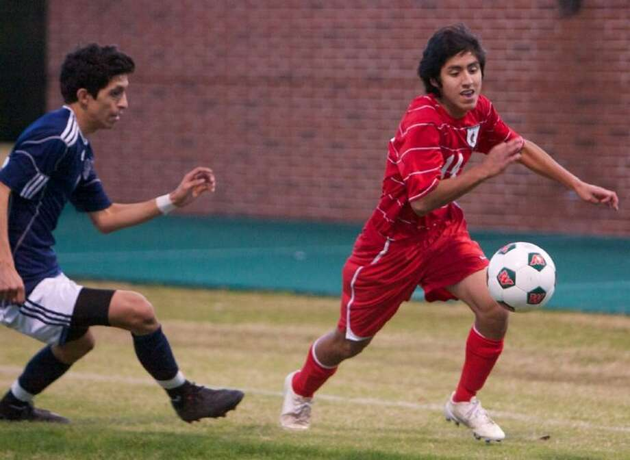 The Woodlands' Fernando Roldan edges against a Cy-Ridge defender during Thursday's tournament game in The Woodlands. Photo: Staff Photo By Eric Swist