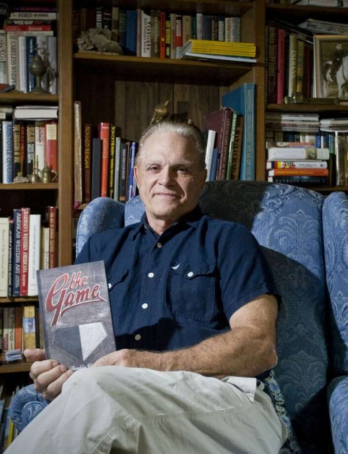 """Author Franklin Kless poses at his home in The Woodlands with a copy of his novel, """"The Game,"""" which recounts a fictionalized version of the first interracial baseball game every played in Vicksburg, Miss."""