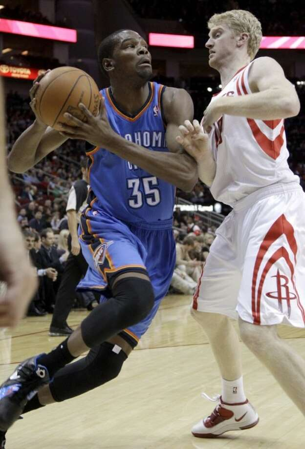 Oklahoma City Thunder's Kevin Durant drives toward the basket as the Houston Rockets' Chase Budinger defends during the first quarter of Wednesday's game in Houston.