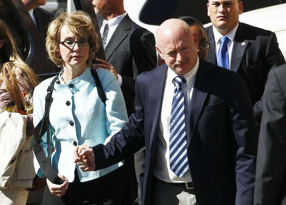 In a Thursday, Nov. 8, 2012 file photo, former Democratic Rep. Gabrielle Giffords, left, and her husband Mark Kelly holds her hand as they leave after the sentencing of Jared Loughner, in back of U.S. District Court, in Tucson, Ariz. Photo: Ross D. Franklin