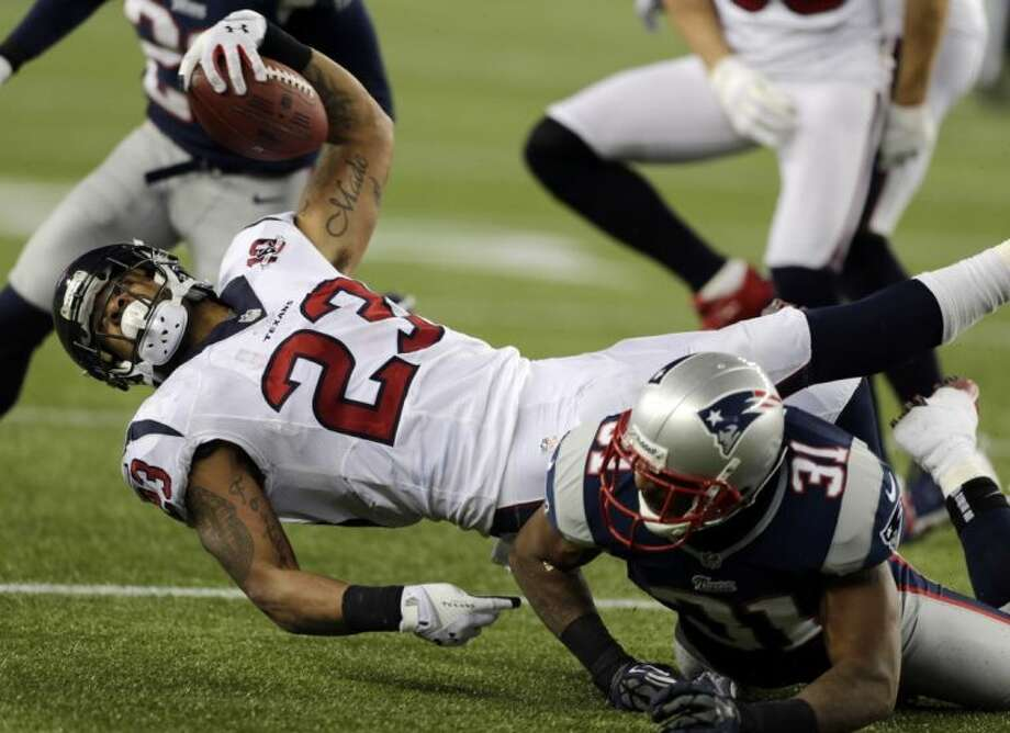 Texans running back Arian Foster reaches forward for a first down after being tackled by New England Patriots cornerback Aqib Talib. The Texans lost 41-28. Photo: Charles Krupa / AP2013