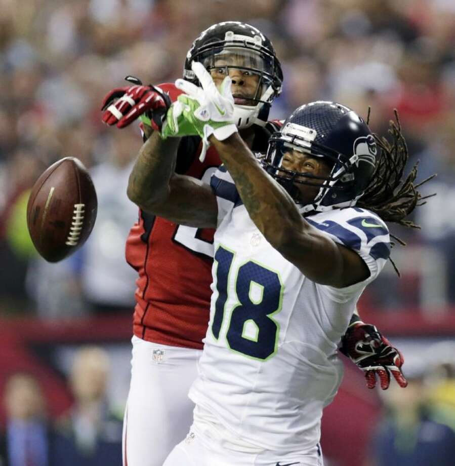 Atlanta Falcons free safety Thomas DeCoud, left, breaks up a pass intended for Seattle Seahawks wide receiver Sidney Rice. The Falcons won 30-28. Photo: Dave Martin / AP2013